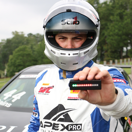 race driver holding apex pro in hand in front of race car
